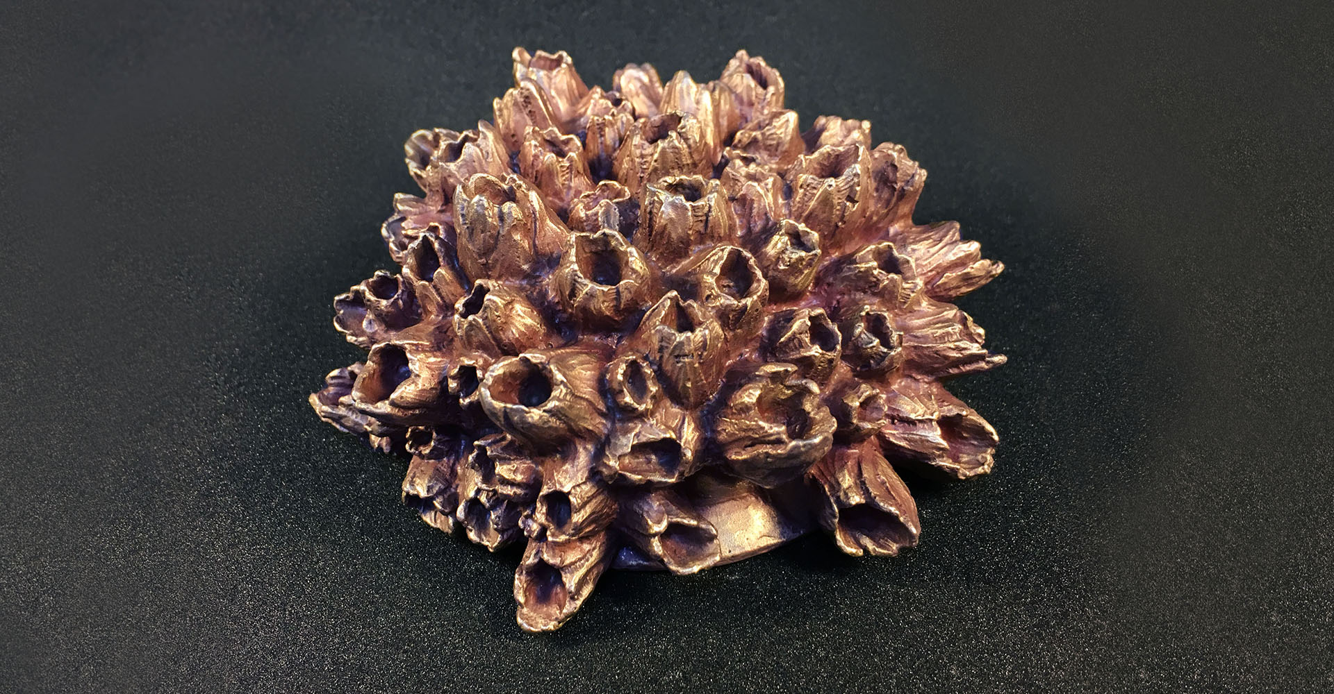Purple barnacle art medal sculpture by artist Kate Ive showing marine nature growing on plastic waste