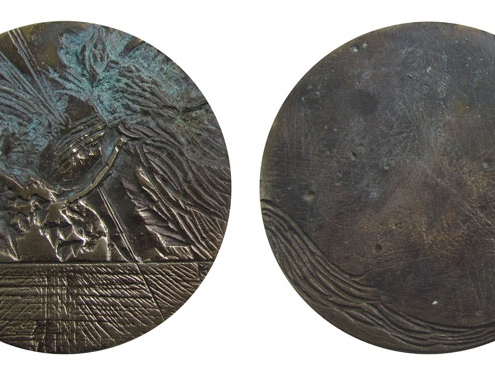 Bronze Animal Art Medal by artist Kate Ive with circular small handheld sculpture with engraved detail with bird of paradise and blue brown patina