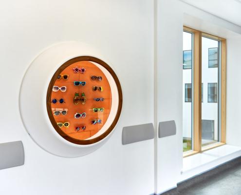 Royal Hospital for Children Artwork sculpture in a wall mounted cabinet, Kate Ive, sunglasses engraved, on an orange brickwork background